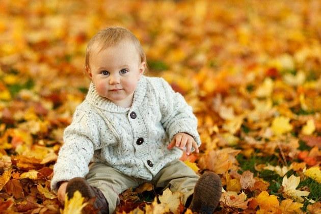 bébé assis dans les feuilles